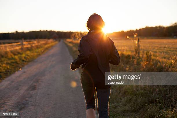 Young woman running on dirt path at sunset