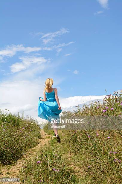 Young woman running on field path