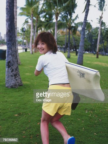Young woman running on lawn with surfboard : Stock Photo