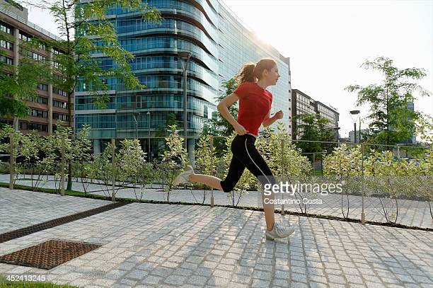 Young woman running past office buildings