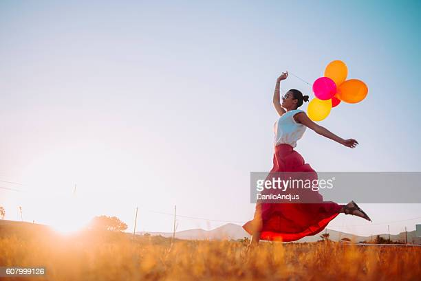young woman running threw the fields holding balloons