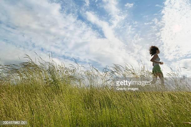 Young woman running through field of long grass