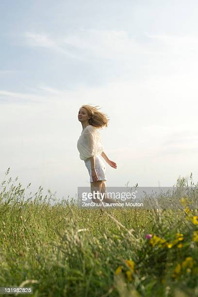 Young woman running through meadow