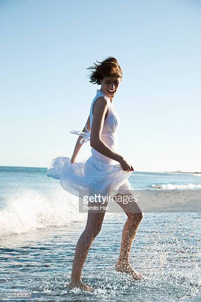 Young woman running through sea, laughing