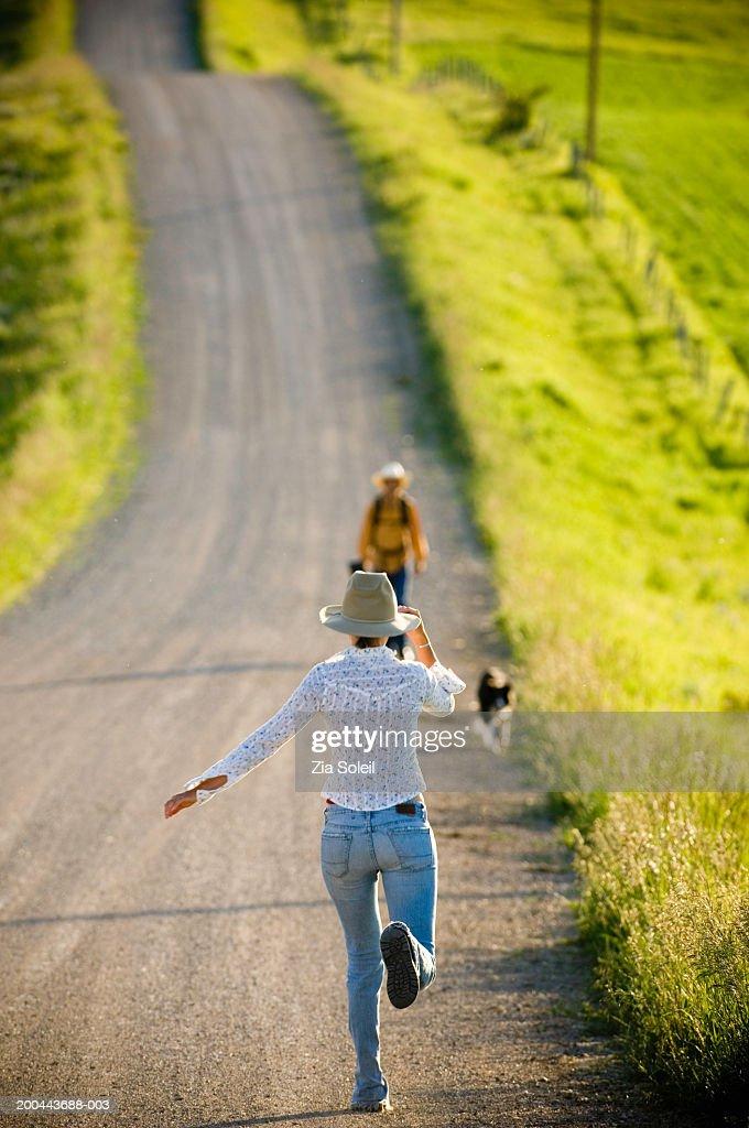 Young woman running toward man walking on rural road, rear view : Stock Photo