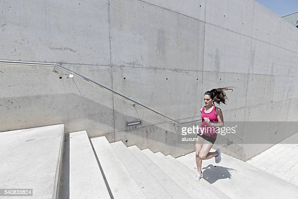 Young woman running upstairs in the city