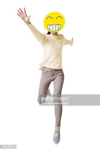 Young woman running with a happy emoticon face in front of her face