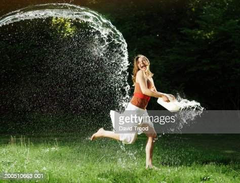 Young woman running with water bucket in garden