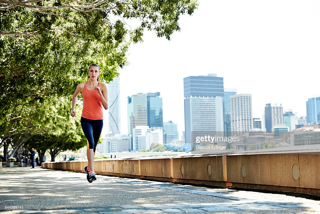 Young woman runs near the city
