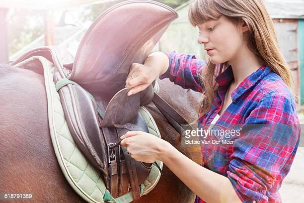 Young woman saddling horse.