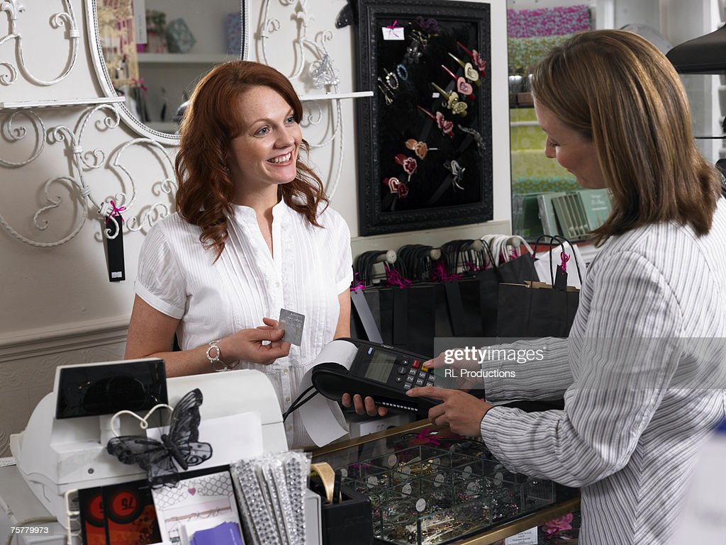 Young woman sales clerk and female customer in gift shop making credit card transaction, smiling : Stock Photo