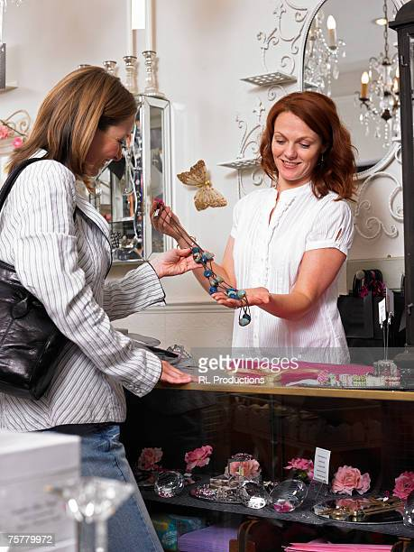 Young woman sales clerk in gift shop presenting necklace to customer, smiling