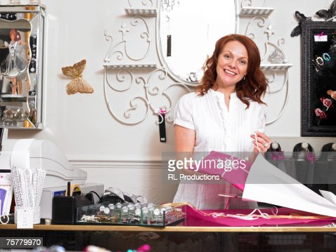 Young woman sales clerk in gift shop standing behind checkout young woman sales clerk in gift shop standing behind checkout counter holding present negle Images