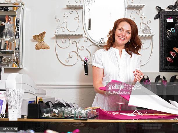 Young woman sales clerk in gift shop, standing behind checkout counter, holding present, smiling