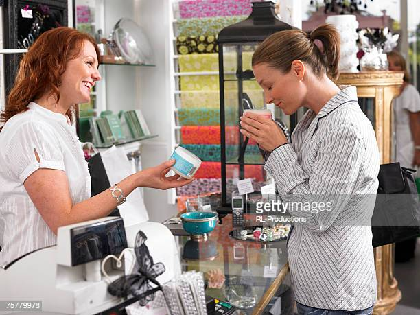 Young woman sales clerk, serving female customer sniffing cosmetics, side view