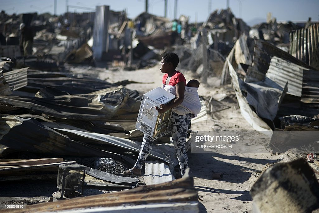A young woman salvages a microwave from the remains of her burnt home after a fire raged through the BM Informal Settlement, in Khayelitsha, on January 1, 2013, in Cape Town. Several unrelated fires ripped through informal settlements in Cape Town killing at least three people and leaving at least 4,000 homeless on New Year's Day, officials said.