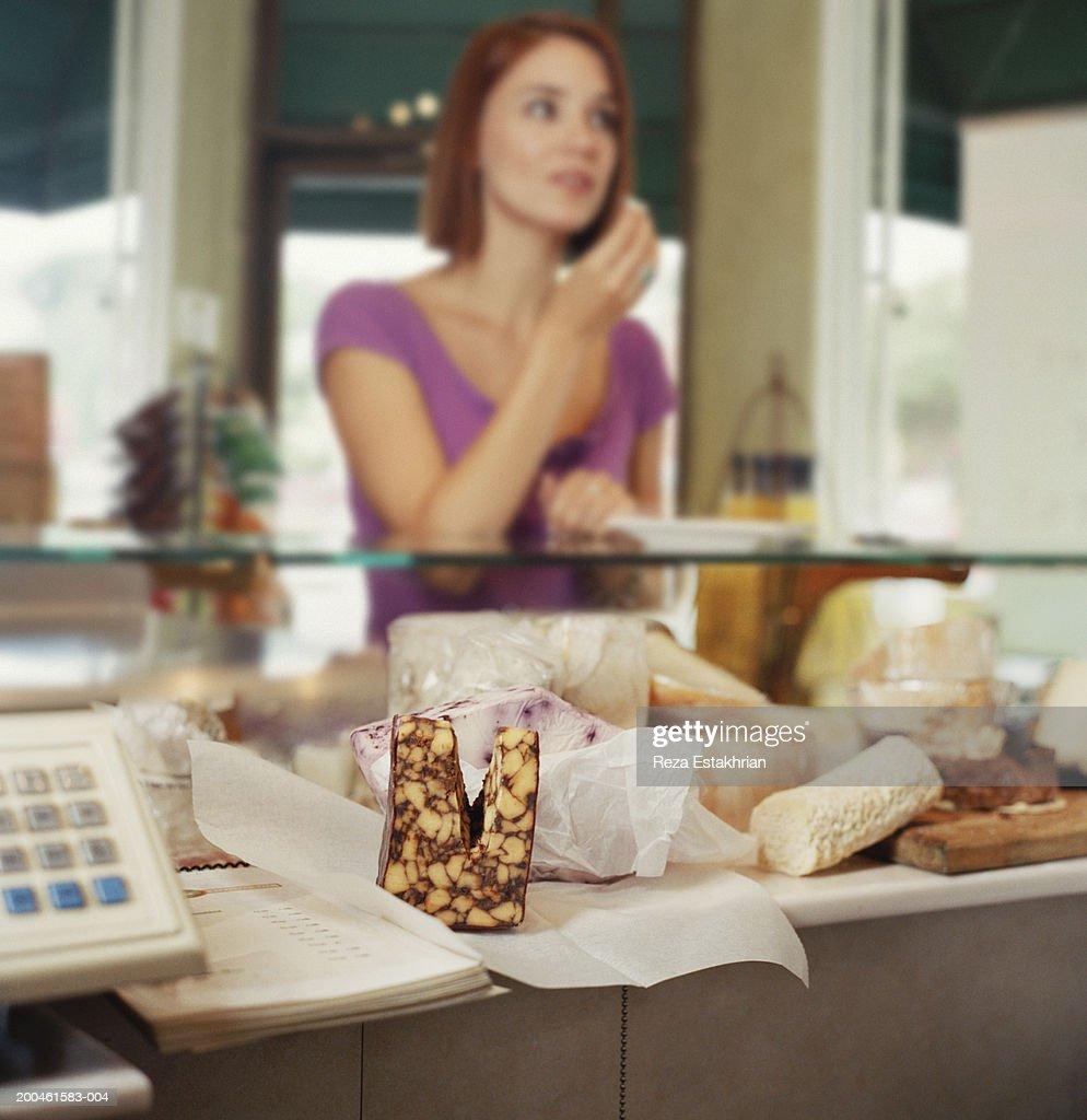 Young woman sampling cheese in gourmet shop : Stock Photo