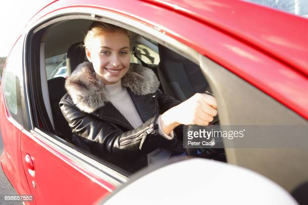 Young woman sat in red car