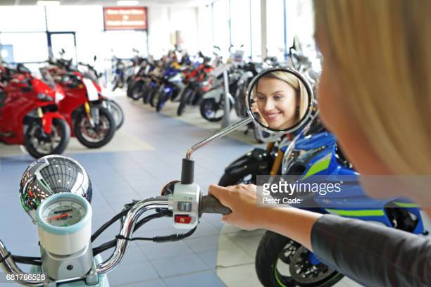 Young woman sat on scooter in showroom, reflection in mirror