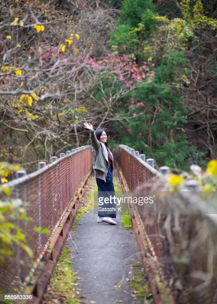 若い女性の狭い橋にさよならを言って