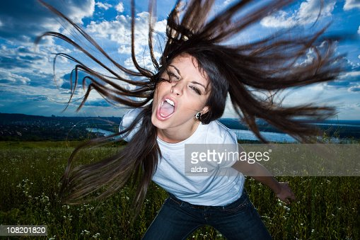 Young Woman Screaming in Field With Hair Flying Everywhere : Stock Photo