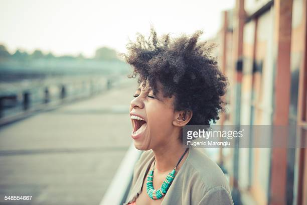 Young woman screaming laughter in city industrial area