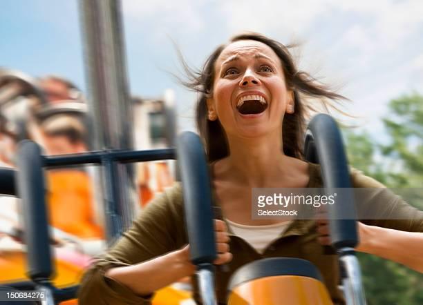 Junge Frau schreien auf einer Achterbahn