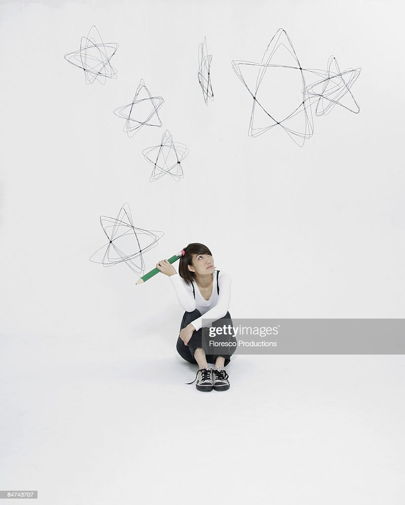Young woman scribbling stars on wall : Stock Photo