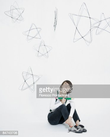 Young woman scribbling stars on wall : Photo