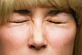 Young woman scrunching face, extreme close-up