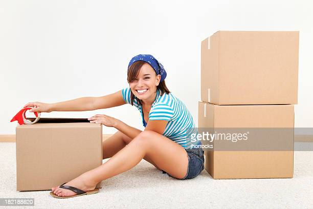 Young Woman Sealing Moving Boxes
