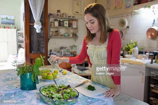 young woman seasoning salad