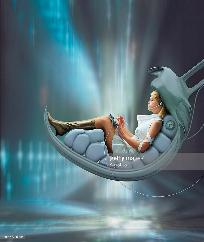 Young woman seated in futuristic chair, typing (Digital Composite) : Stock Photo