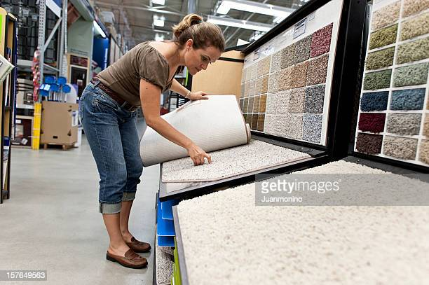 A young woman selecting a carpet samples
