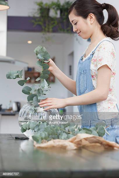 Young woman selecting foliage for vase arrangement