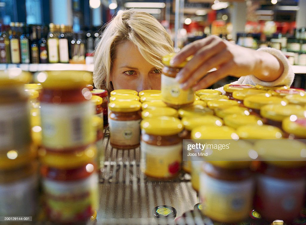Young woman selecting jar from shelf in shop (focus on woman's face) : Stock Photo