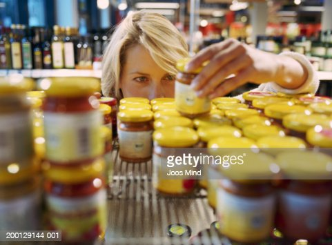 Young woman selecting jar from shelf in shop (focus on woman's face) : Photo