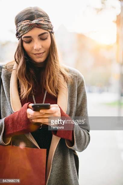 Junge Frau du eine sms mit einem Smartphone.