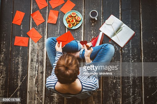Young woman sending a valentine card - top view