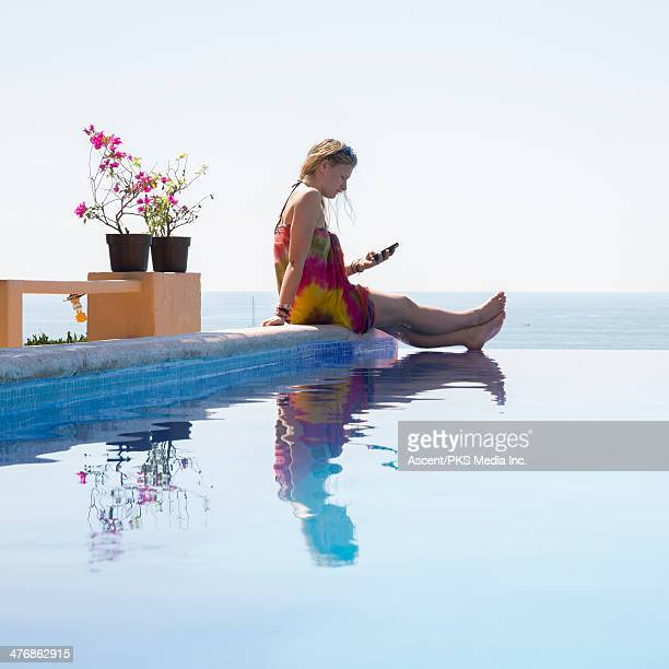 Young woman sends text at edge of infinity pool