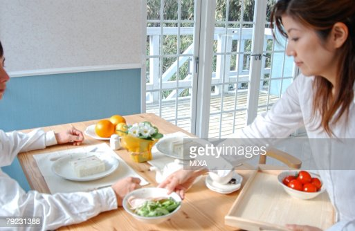 A young woman serving breakfast : Stock Photo