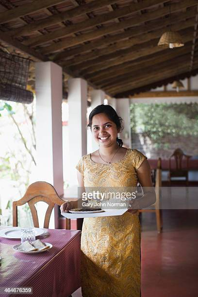 Young woman serving dinner at Homestay in India