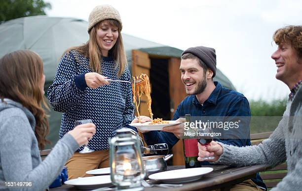 Young woman serving pasta to fellow glampers.