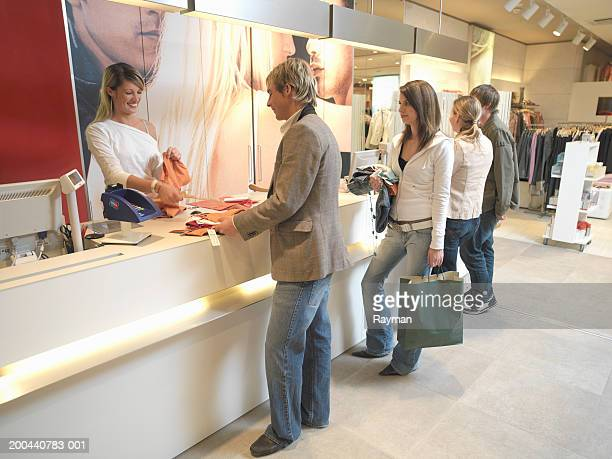 Young woman serving queue of customers in clothes shop, smiling