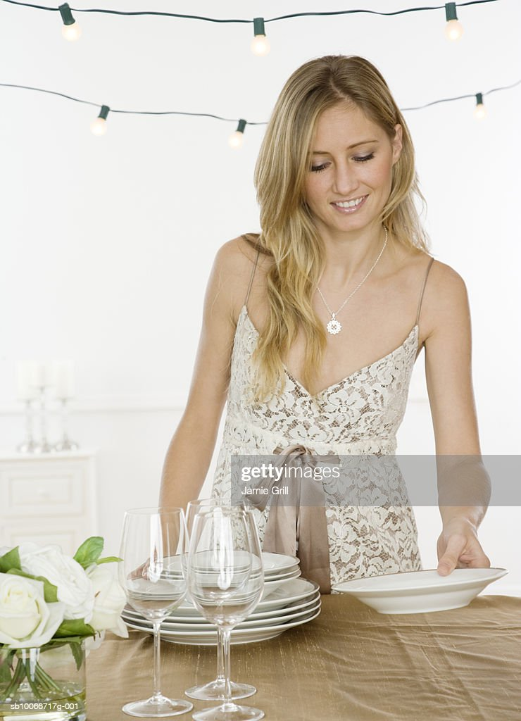 Young woman setting dinner table for party, smiling (focus on foreground) : Stock Photo