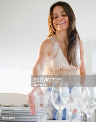 Young woman setting table, smiling : Stock Photo