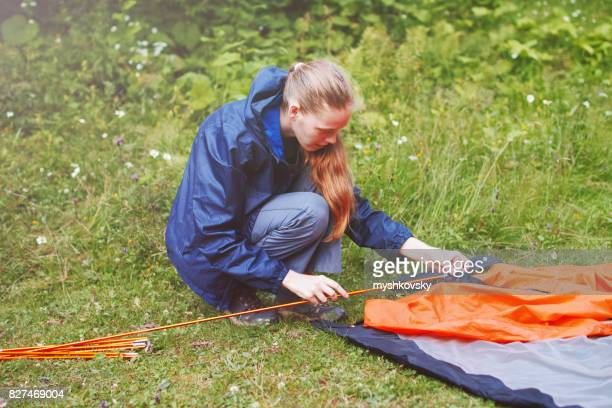 Young woman setting up a tourist tent.