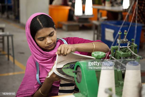 A young woman sews a sweater on the factory floor at Syntex Knitwear on February 27 2103 Company officers say they strictly enforce fire safety...