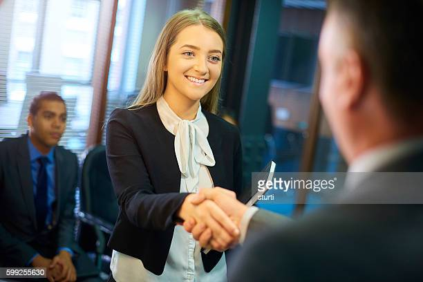 young woman shakes hands at interview
