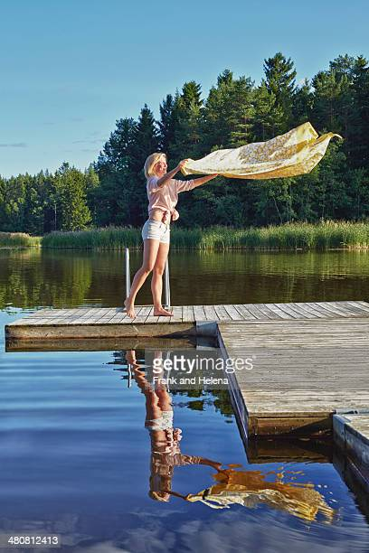 Young woman shaking blanket on pier, Gavle, Sweden